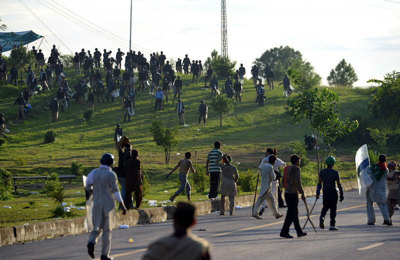 . Pakistani supporters of cricketer-turned politician Imran Khan and Canadian cleric Tahir ul Qadri chase riot police during an anti-government protest in Islamabad on September 1, 2014. Hundreds of protesters trying to topple Pakistan\'s government briefly seized the state broadcaster on September 1, intensifying the political crisis gripping the nuclear-armed nation. Deadly clashes since the weekend have raised the specter of military intervention which gained ground after one disillusioned opposition leader said the protesters were acting according to a plan devised by the army. AAMIR QURESHI/AFP/Getty Images