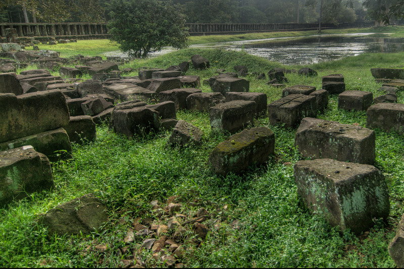Moss covered rocks scattered near stream in Angkor Wat