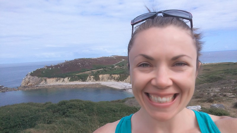 woman smiling with coastal scene in the background