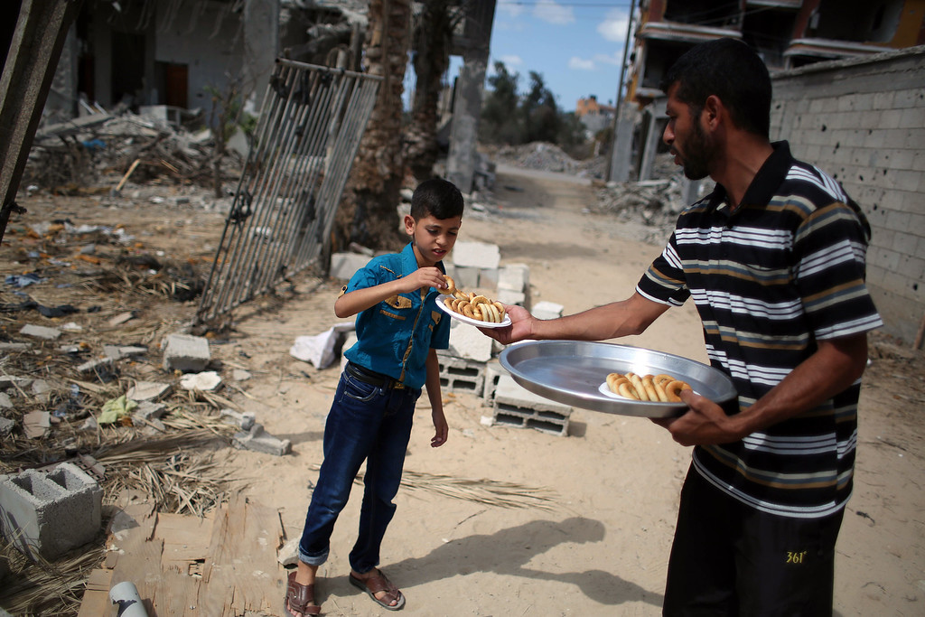 . Ahmed (R) distributes traditional date-filled cookies ahead of the Eid al-Adha celebrations on October 2, 2014, in Khan Yunis\' Khuzaa neighbourhood in the southern Gaza Strip. Muslims across the world are preparing to celebrate the annual festival of Eid al-Adha, or the Festival of Sacrifice, which marks the end of the Hajj pilgrimage to Mecca and commemorates Prophet Abraham\'s readiness to sacrifice his son to show obedience to God. SAID KHATIB/AFP/Getty Images