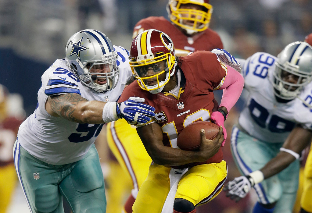 . Washington Redskins quarterback Robert Griffin III (10) is sacked by Dallas Cowboys defensive tackle Nick Hayden (96) in the first half of an NFL football game, Sunday, Oct. 13, 2013, in Arlington, Texas. (AP Photo/Tim Sharp)