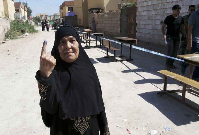 . An elderly Iraqi woman shows her ink-stained finger after casting her vote outside a polling station in Habaniyah town, near Fallujah Iraq, Wednesday, April 30, 2014. Local police reported several mortar attacks in Amiriyat al-Fallujah and  Habaniyah town near Fallujah, near some voting centers that led to the injury of two persons. Iraq is holding its third parliamentary elections since the U.S.-led invasion that toppled dictator Saddam Hussein. (AP Photo)