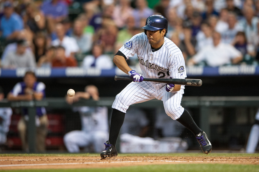 . DENVER, CO - JULY 24:  Jorge De La Rosa #29 of the Colorado Rockies hits a successful sacrifice bunt to move the runner to second base in the fifth inning of a game against the Miami Marlins at Coors Field on July 24, 2013 in Denver, Colorado. (Photo by Dustin Bradford/Getty Images)