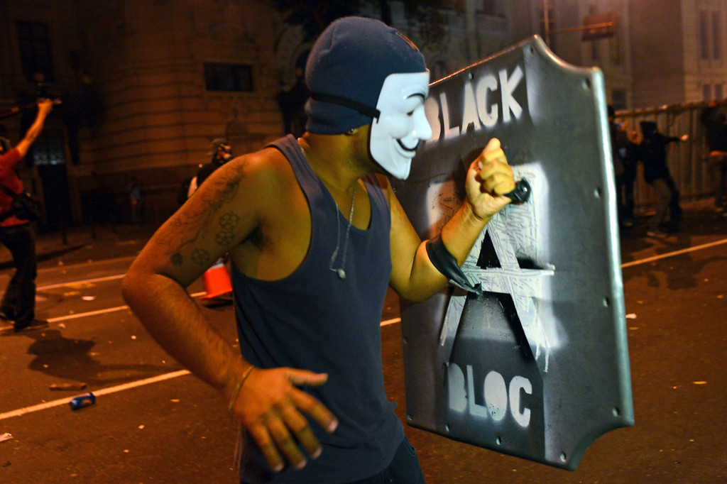""". A demonstrator with the Guy Fawkes mask clashes with the police during the \""""Teachers\' day\"""" protest in demand of better working conditions and against police violence, on October 15, 2013 in Rio de Janeiro, Brazil. AFP PHOTO / CHRISTOPHE  SIMON/AFP/Getty Images"""