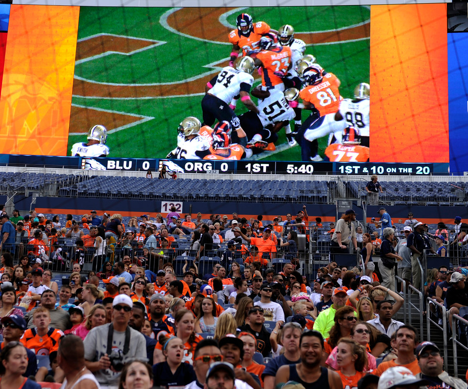 . DENVER, CO. - AUGUST 03: Fans watch highlights from last season before the rain hit Saturday night. Denver Broncos fans waited inside Sports Authority Field Saturday night, August 3, 2013 hoping the weather would clear so that the team could practice.  Photo By Karl Gehring/The Denver Post