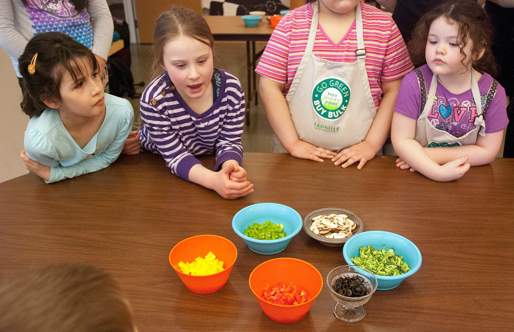 . Kayla Rice/Reformer Children check out their topping options during a pizza cooking class held at the Brattleboro Food Co-Op for the Winter Carnival on Friday afternoon.