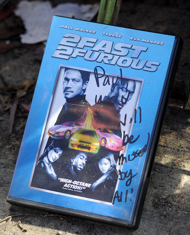""". A \""""2 Fast 2 Furious\"""" DVD at the memorial for Paul Walker and Roger Rodas, Sunday, December 1, 2013, at the scene of their fatal crash site in Valencia. (Photo by Michael Owen Baker/L.A. Daily News)"""