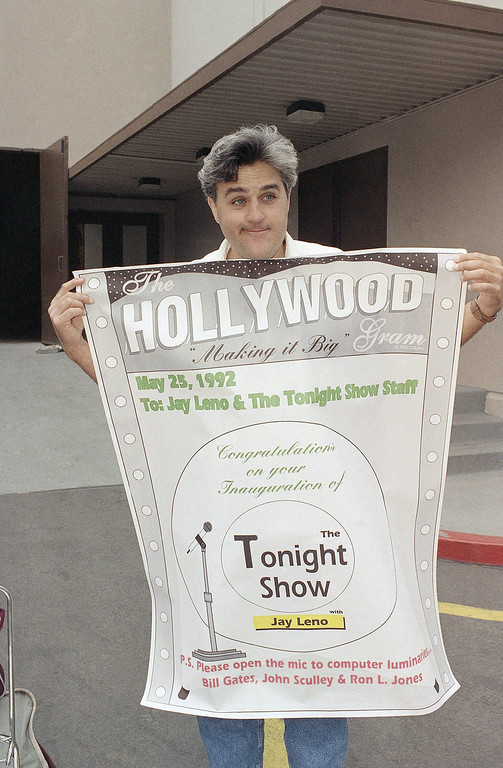 """. Jay Leno holds up a sign congratulating him on the inauguration of \""""The Tonight Show with Jay Leno,\"""" outside the NBC Studios in Burbank, Calif., May 25, 1992. A fan from Palo Alto, Calif., made the sign and presented it to Leno while waiting in line to see the first show Monday night. Leno took over as host of the show after Johnny Carson retired. (AP Photo/Kevork Djansezian)"""
