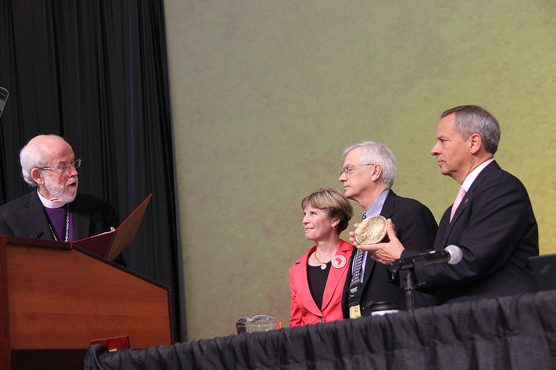 Presiding Bishop Mark S. Hanson and Carlos E. Peña, vice president of the ELCA, present the Servus Dei Medal to David Swartling, secretary of the ELCA. Barbara Swartling stands by his side.
