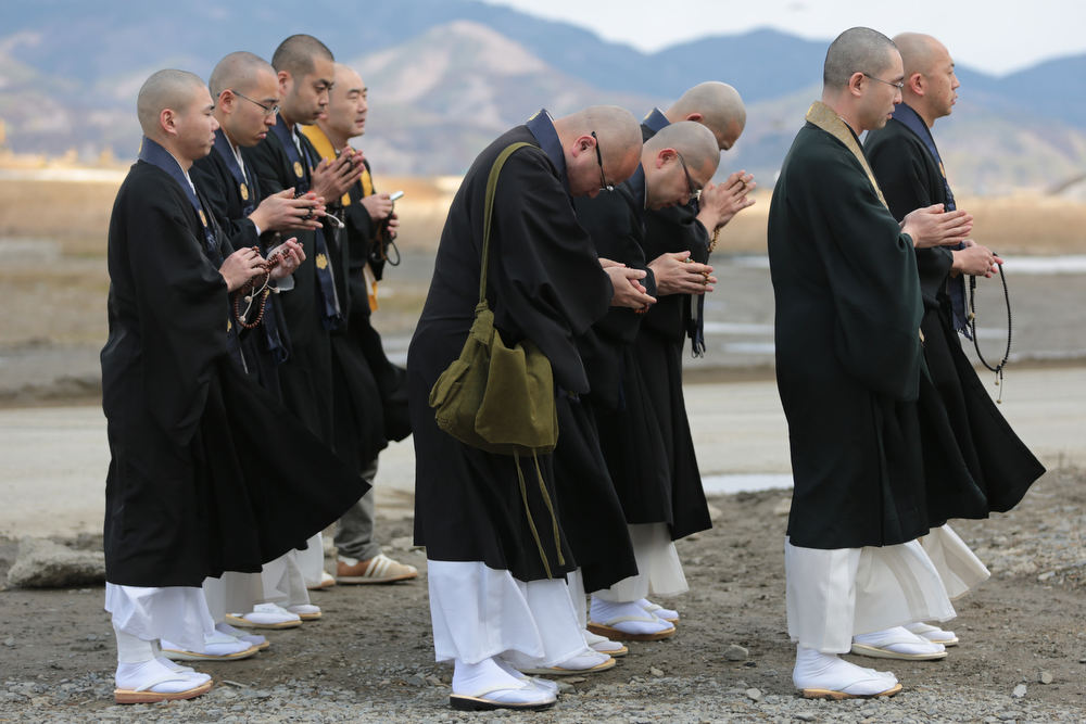 . Buddhist monks offer prayers at Okawa Elementary School on the three year anniversary of the earthquake and tsunami on March 11, 2014 in Ishinomaki, Miyagi prefecture, Japan. On March 11 Japan commemorates the third anniversary of the magnitude 9.0 earthquake and tsunami that claimed more than 18,000 lives, and subsequent nuclear disaster at the Fukushima Daiichi Nuclear Power Plant.  (Photo by Yuriko Nakao/Getty Images)