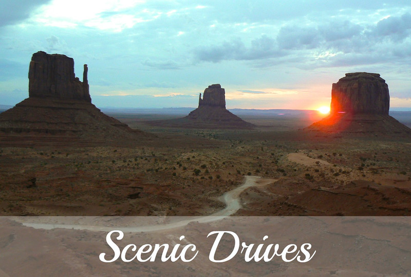 The sun rises behind red sandstone monoliths as a road winds through Monument Valley on one of our favorite scenic drives.