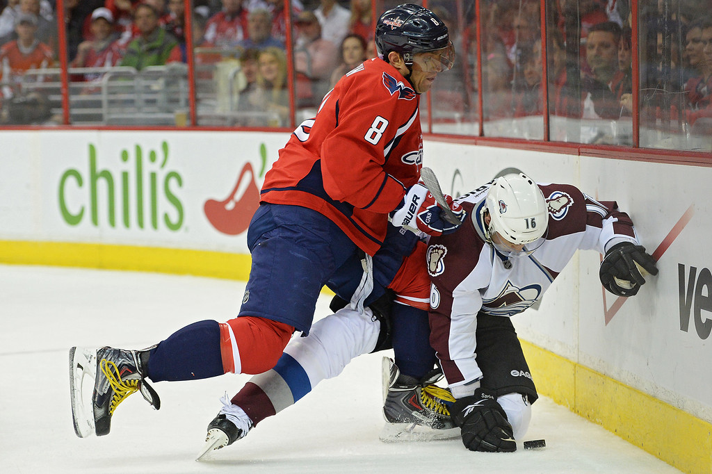 . WASHINGTON, DC - OCTOBER 12: Alex Ovechkin #8 of the Washington Capitals hits Cory Sarich #16 of the Colorado Avalanche into the boards in the first period at Verizon Center on October 12, 2013 in Washington, DC. (Photo by Patrick Smith/Getty Images)