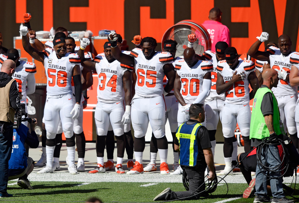 . Members of the Cleveland Browns hold their arms up in protest during the national anthem before an NFL football game against the Cincinnati Bengals, Sunday, Oct. 1, 2017, in Cleveland. (AP Photo/David Richard)