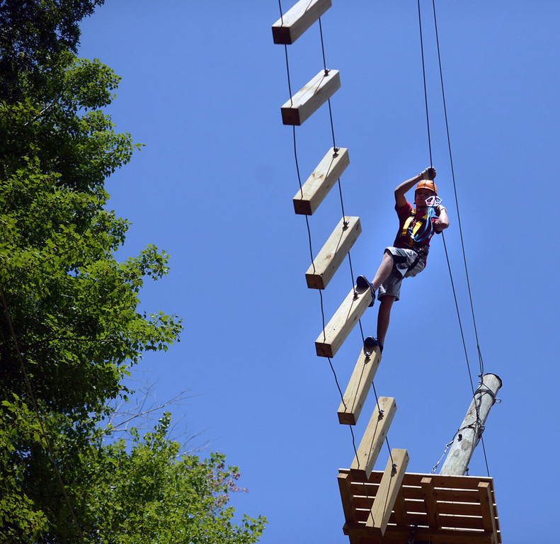 . A boy carefully crosses a series of wooden pegs about 40 feet high in the expert portion of the challenge course at the Aerial Adventure Park at Trollhaugen. (Pioneer Press: Chris Polydoroff)