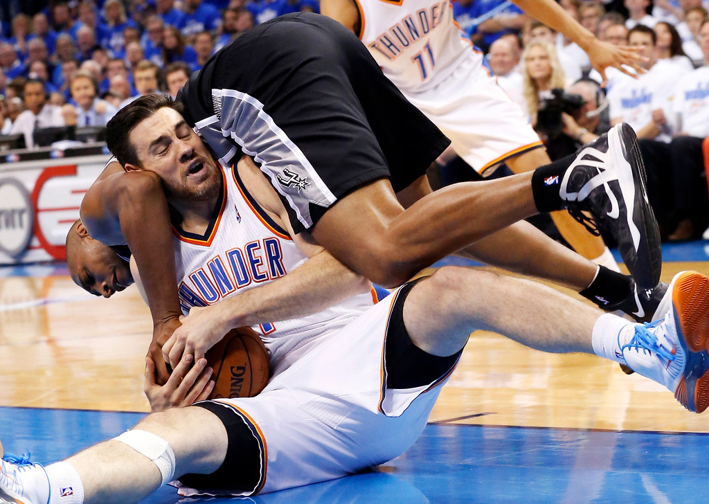 . San Antonio Spurs forward Boris Diaw, top, dives over Oklahoma City Thunder forward Nick Collison to try and take the ball in the fourth quarter of Game 4 of the Western Conference finals NBA basketball playoff series in Oklahoma City, Tuesday, May 27, 2014.  (AP Photo/Sue Ogrocki)