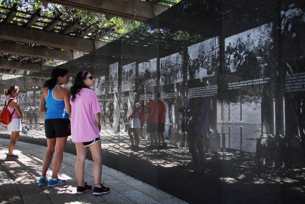 Description of . (L-R) Dana Greenberg, Tricia Miner and Ilyse Greenberg look at pictures on display as they visit the Holocaust Memorial during Yom HaShoah-Holocaust Remembrance Day on April 8, 2013 in Miami Beach, Florida. Holocaust Remembrance Day is observed as a day of commemoration for the approximately six million Jews who died during the Holocaust.  (Photo by Joe Raedle/Getty Images)