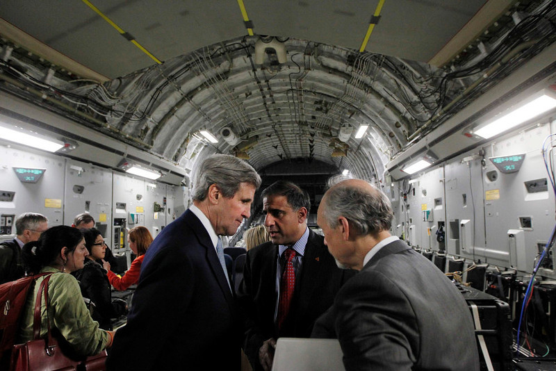 . U.S. Secretary of State John Kerry speaks with Puneet Talwar (C), the National Security Council\'s Senior Director with responsibilities for Iran, Iraq, and the Gulf countries, and another advisor aboard an Air Force C-17 aircraft during their return to Amman from a trip to Baghdad March 24, 2013. Kerry made an unannounced visit to Iraq on Sunday and said he told Prime Minister Nuri al-Maliki of his concern about Iranian flights over Iraq carrying arms to Syria.   REUTERS/Jason Reed