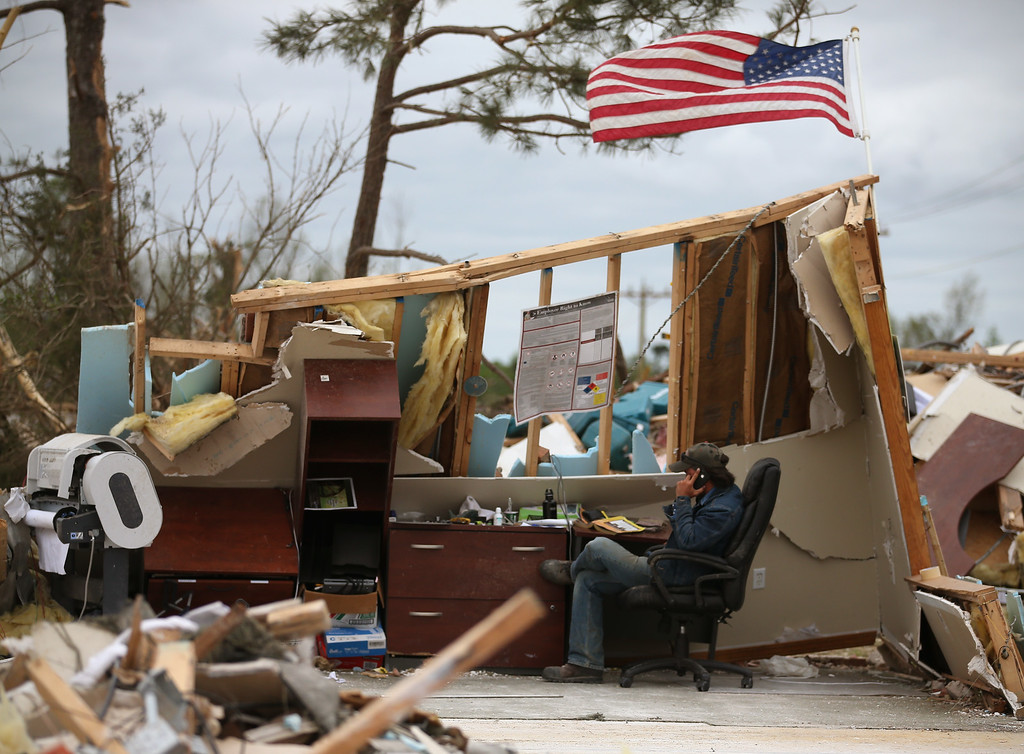 . A man who wished not to be identified talks on a phone in a business that was destroyed by a tornado, April 30, 2014 in Mayflower, Arkansas. Deadly tornadoes ripped through the region starting on April 27 leaving more than two dozen dead. The storm system has also brought severe flooding to Florida\'s Panhandle.  (Photo by Mark Wilson/Getty Images)