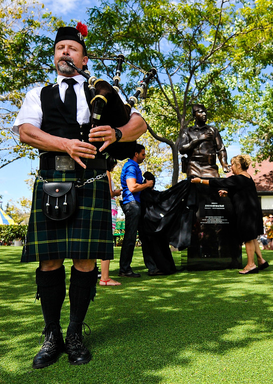 . Steve Moeller plays a bagpipe solo in honor of slain San Bernardino County Sheriff\'s Deputy Jeremiah MacKay as sculptor Khachik Khachatouryan (cq), center, unveils the Jeremiah MacKay bronze statue in front of friends, family and the public at the Lake Arrowhead Village in Lake Arrowhead on Sunday, Sept. 1, 2013. San Bernardino County Sheriff\'s Detective MacKay was killed on Feb. 12 in a gun battle with fugitive ex-cop Christopher Dorner near Big Bear during a massive manhunt in search of Dorner. (Rachel Luna / Staff Photographer)