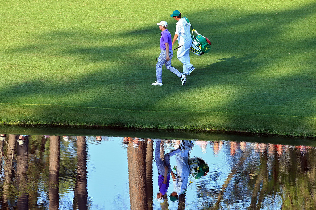. Jonas Blixt of Sweden walks to the 16th green with his caddie Zak Williamson during the third round of the 2014 Masters Tournament at Augusta National Golf Club on April 12, 2014 in Augusta, Georgia.  (Photo by David Cannon/Getty Images)