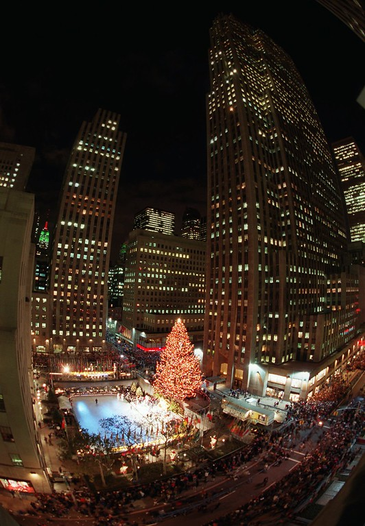 . The skyscrapers of New York\'s Rockefeller Center surround a 75-foot high,  63-year-old,  Norway Spruce after it was illuminated Tuesday, Dec. 5, 1995.   Naomi Campbell, Elle Macpherson, Claudia Schiffer and Christy  Turlington  flipped a switch to light more than 25,000  multicolored bulbs strung over five miles of electrical wire above the  center\'s ice-skating rink. They were joined by a contingent of  nuns from the Sisters of Christian Charity  - the former owners of the tree. (AP Photo/Adam Nadel)
