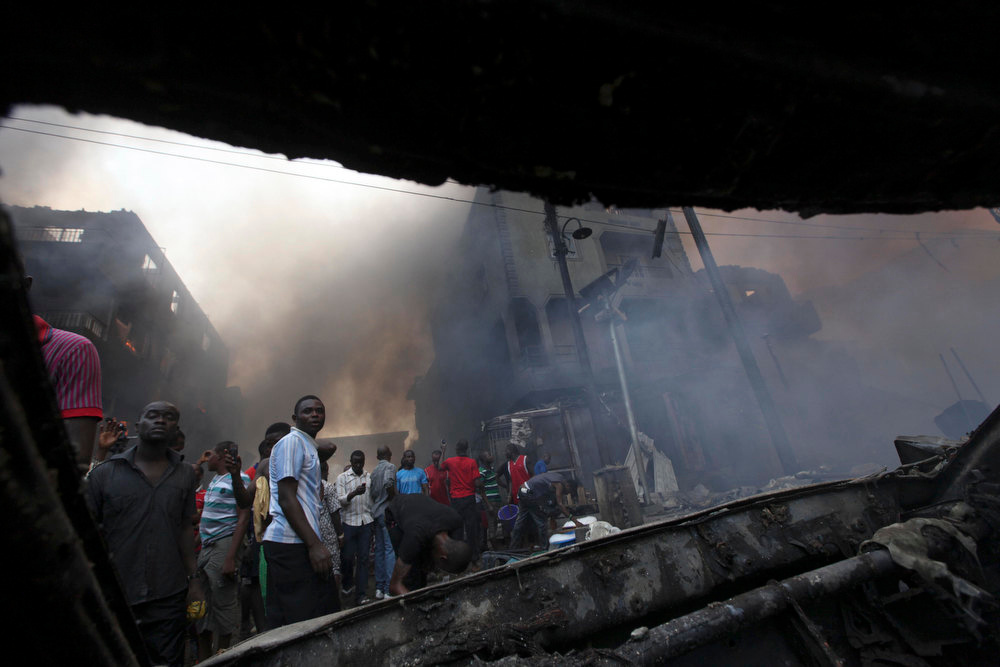 Description of . Residents are seen from a burnt out car at a residential homes and a warehouse fire  on Lagos Island in Lagos, Nigeria, Wednesday, Dec. 26, 2012. An explosion ripped through a warehouse Wednesday where witnesses say fireworks were stored in Nigeria's largest city, sparking a fire. It wasn't immediately clear if anyone was injured in the blast that firefighters and locals struggled to contain. (AP Photos/Sunday Alamba)