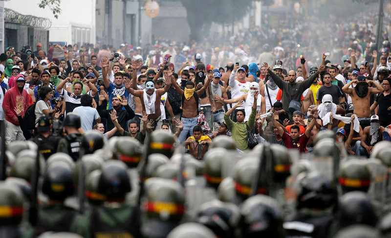 . Supporters of opposition leader Henrique Capriles face off against riot police as they demonstrated for a recount of the votes in Sunday\'s election, in Caracas, April 15, 2013. Hundreds of protesters clashed with police in the Venezuelan capital on Monday after Capriles called for demonstrations to demand a recount of votes from Sunday\'s election to replace the late Hugo Chavez. REUTERS/Christian Veron