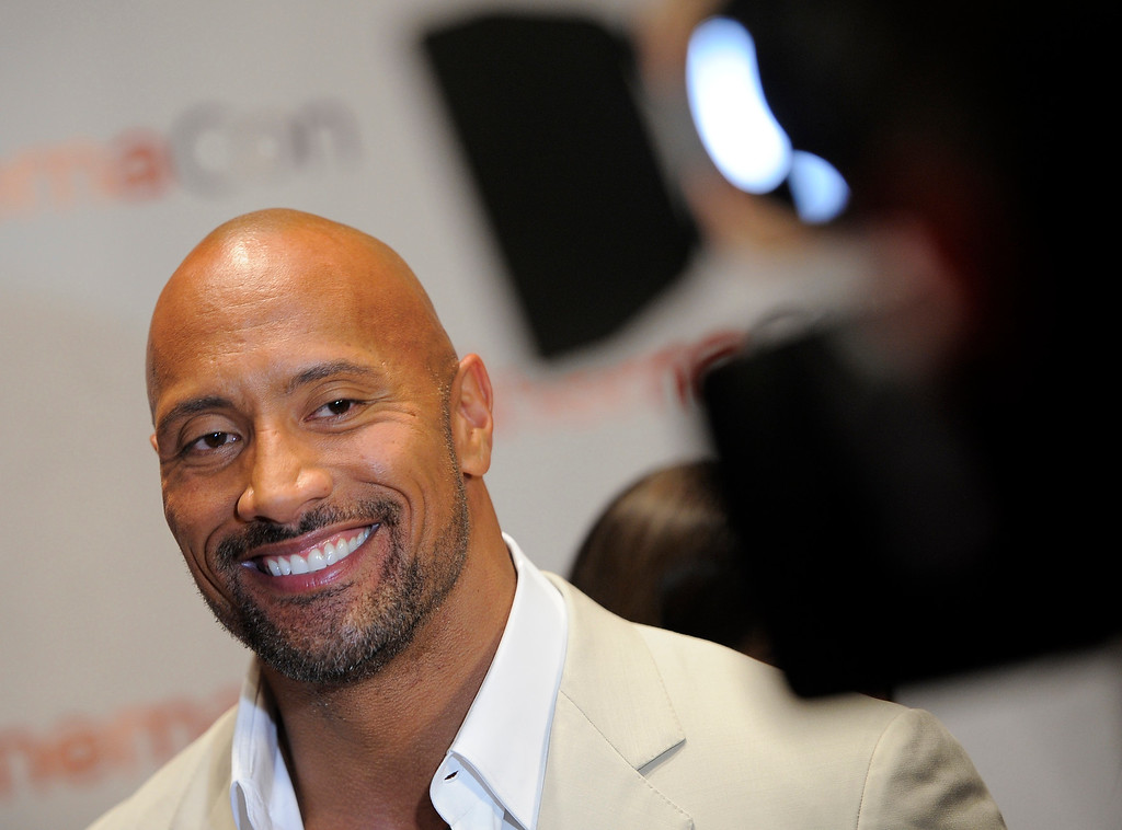 """. Dwayne Johnson, a cast member in the upcoming film \""""G.I. Joe: Retaliation,\"""" smiles during an interview on the opening night of CinemaCon 2012, the official convention of the National Association of Theater Owners, Monday, April 23, 2012. (AP Photo/Chris Pizzello)"""