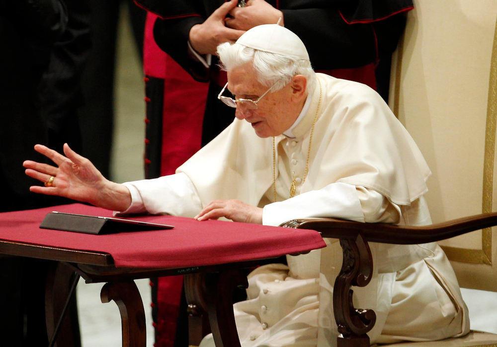 Description of . Pope Benedict XVI reacts after posting his first tweet using an iPad tablet after his Wednesday general audience in Paul VI's Hall at the Vatican December 12, 2012. REUTERS/Giampiero Sposito