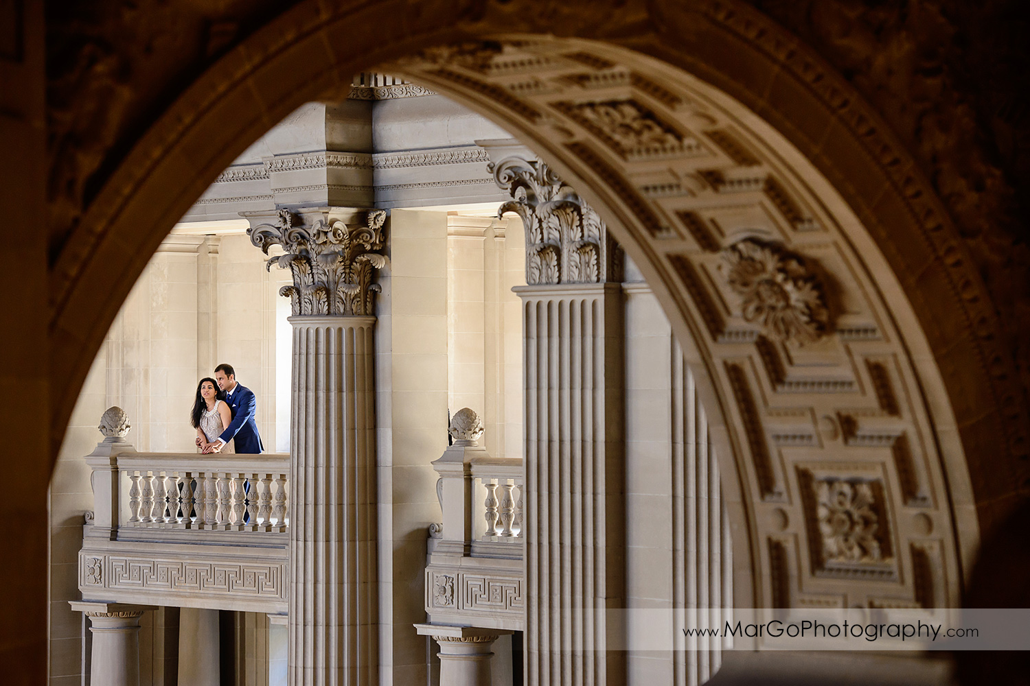 woman in beige dress and man in navy blue suit seen through the arch on the third floor of San Francisco City Hall