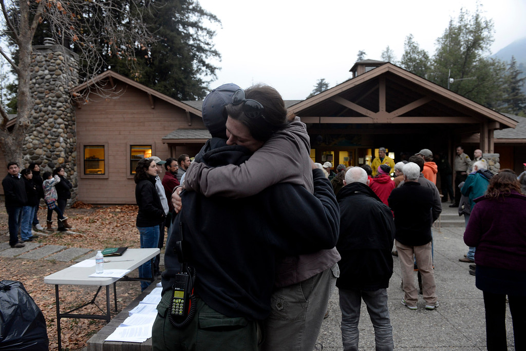 . Big Sur resident Alicia Hahn hugs U.S. Forest Service firefighter Kevin Murray during the evening community meeting at the Big Sur Station in Big Sur, Calif. on Wednesday December 18, 2013. (Photo David Royal/ Monterey County Herald)