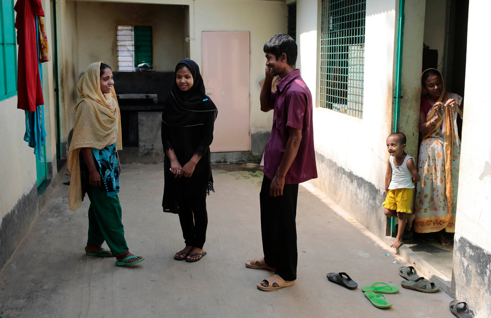 . In this Tuesday, April 22, 2014 photo, Reshma Begum, center, who survived for 17 days in the rubble of a collapsed Rana Plaza garment factory, talks to relatives at her sister\'s home in Savar, near Dhaka, Bangladesh. When the building began crumble around her, Begum said she raced down a stairwell into the basement, where she became trapped near a wide pocket that allowed her to survive. Although her story has a happy ending, she now works in an international hotel in Dhaka\'s upscale Gulshan area, Begum is still haunted by the disaster. (AP Photo/A.M. Ahad)