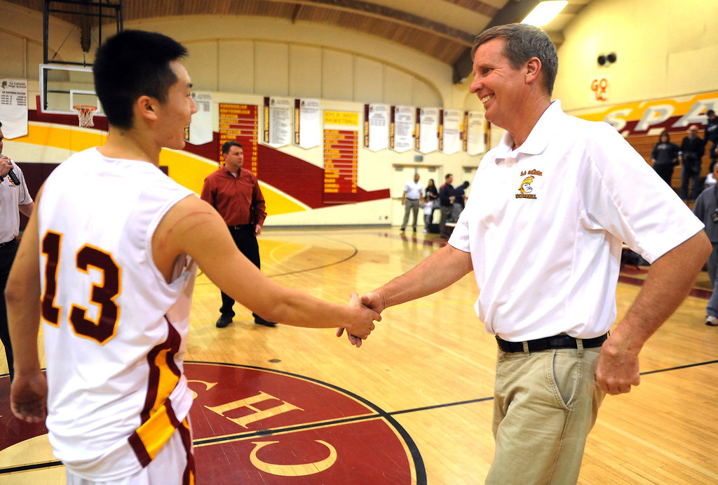 . La Canada head coach Tom Hofman shakes hands with Dan Jun (13) after winning his 600th game as they defeated La Salle 73-62 during a prep basketball game at La Canada High School in La Canada, Calif., on Friday, Jan. 10, 2014. Hofman record is 600 wins and 186 losses since becoming varsity head coach in the 1986-87 season. (Keith Birmingham Pasadena Star-News)