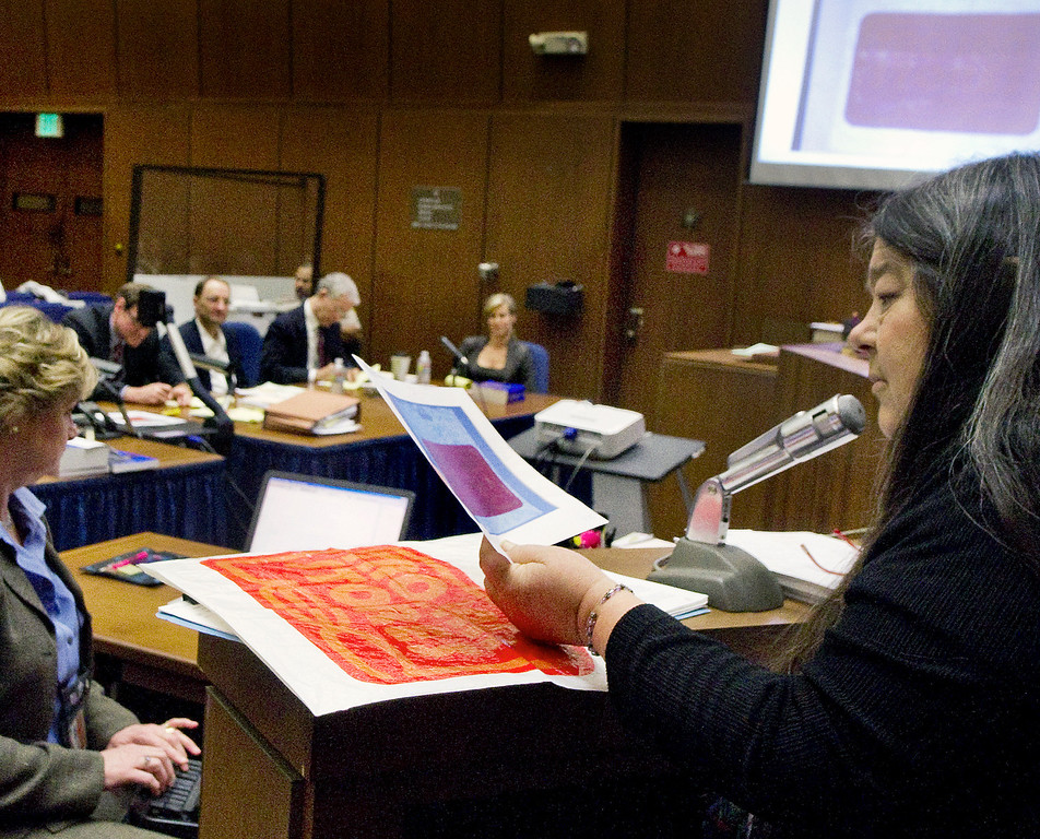 """. Lynne Herold,  forensic scientists who examined the remains of John Sohus and Gerhartsreiter guest house for trace evidence in 1994 looking at a photograph of a Wisconsin plastic bag from the crime scene in San Marino at at the murder trial of Christian Gerhartsreiter, 52,  known as \""""Clark\"""" Rockefeller, second day at trial at Clara Shortridge Fortz Criminal Justice Center in Los Angeles on Wednesday March 20, 2013.  Gerhartsreiter is a German immigrant who masqueraded as a member of the Rockefeller family. He is charged with murder of John Sohus, 27, whose bones were unearthed from the backyard of the home in San Marino, California, in 1985.  Sohus\' wife, Linda, has never been found. (SGVN/Photo by Walt Mancini/LANG)"""