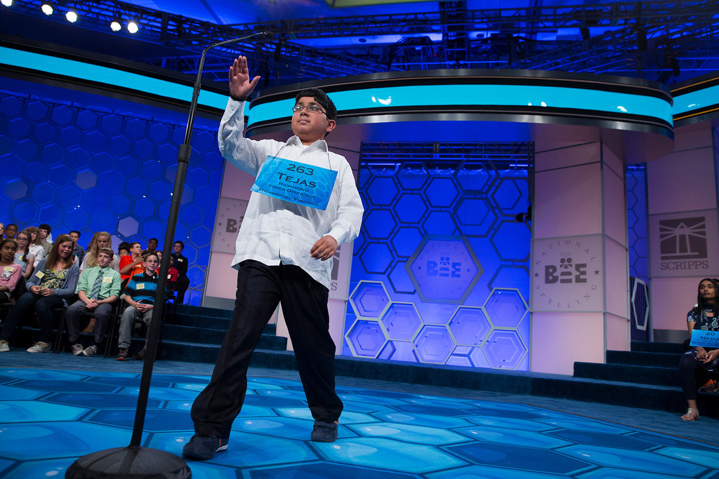 ". Tejas Muthusamy, 11, of Glen Allen, Va., reaches for the microphone before spelling the word ""gematria\"" during the final round of the National Spelling Bee, on Thursday, May 29, 2014, in Oxon Hill, Md. (AP Photo/ Evan Vucci)"