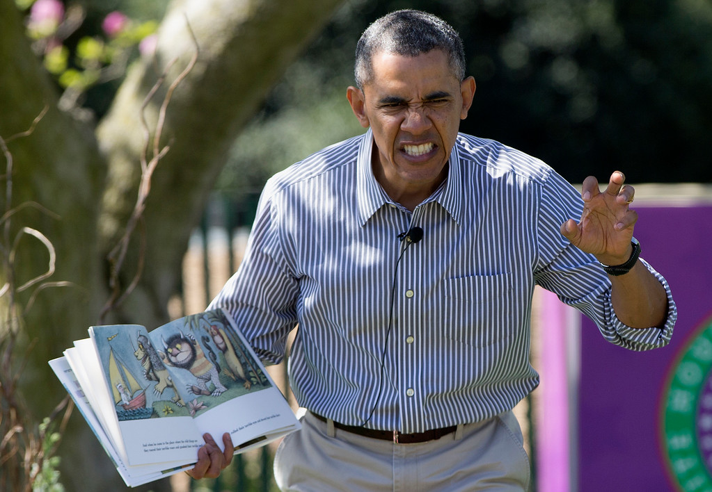 """. President Barack Obama makes a face as he reads \""""Where the Wild Things Are\"""" by Maurice Sendak, during the White House Easter Egg Roll on the South Lawn of the White House is Washington, Monday, April 21, 2014. Thousands of children gathered at the White House for the annual Easter Egg Roll. This year\'s event features live music, cooking stations, storytelling, and of course, some Easter egg rolling. (AP Photo/Carolyn Kaster, File)"""