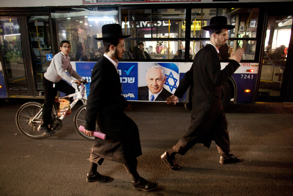 Description of . Ultra Orthodox Jews walk past a bus as an election poster of Israeli Prime Minister Benjamin Netanyahu hang on it, ahead of the upcoming Israeli elections on January 21, 2013 in Bnei Brak, Israel. Israeli elections are scheduled for January 22 and so far showing a majority for the Israeli right.  (Photo by Uriel Sinai/Getty Images)