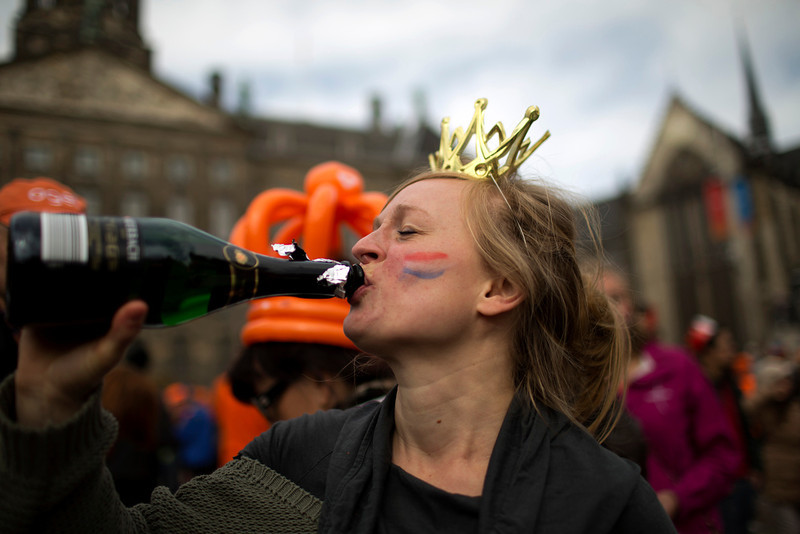 . A woman drinks after watching King Willem-Alexander, Queen Maxima and Princess Beatrix sign the act of abdication outside the Royal Palace in Amsterdam, The Netherlands, Tuesday April 30, 2013. Around a million people are expected to descend on the Dutch capital for a huge street party to celebrate the first new Dutch monarch in 33 years.  (AP Photo/Emilio Morenatti)