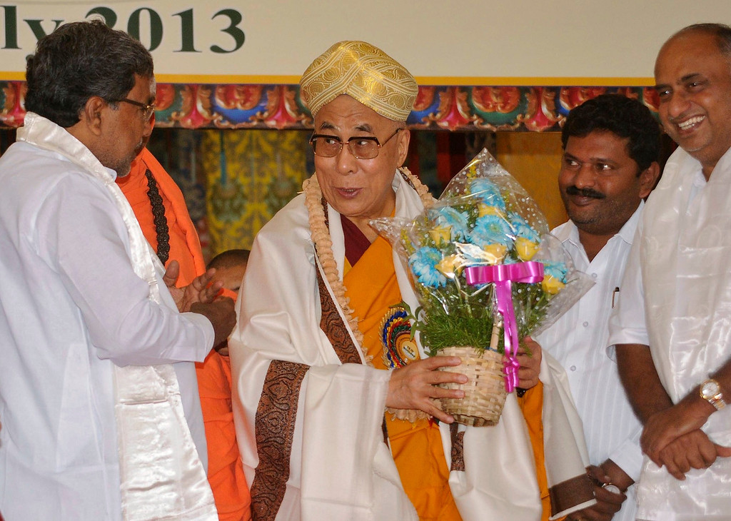 . Exiled Tibetan spiritual leader the Dalai Lama (C) interacts with Chief Minister of India\'s Karnataka state K. Siddaramaiah (L) during the Dalai Lama\'s 78th birthday celebrations at Bylakuppe, about 213 km (132 miles) south of the southern Indian city of Bangalore July 6, 2013. REUTERS/Stringer
