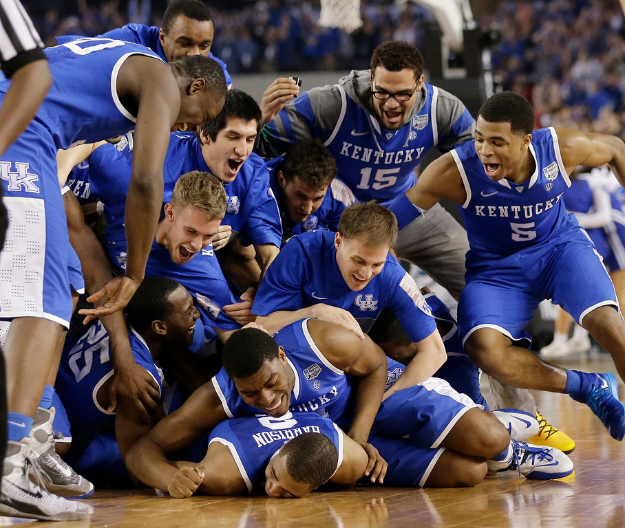 . Kentucky players celebrate on the court after their 74-73 victory over Wisconsin in an NCAA Final Four tournament college basketball semifinal game Saturday, April 5, 2014, in Arlington, Texas. (AP Photo/Eric Gay)