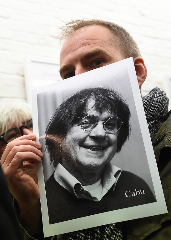 . Belgian cartoonist DuBus holds a photograph of slain French cartoonist Jean Cabut (also known by his pen-name Cabu) in Brussels on January 8, 2015 as he and other cartoonists gather to pay homage to French cartoonists killed in the attack against French satirical newspaper Charlie Hebdo that killed 12 people.    French security forces were Thursday frantically hunting two brothers suspected of gunning down 12 people in an Islamist attack on a satirical weekly, as a stunned and outraged France fell silent to mourn the victims.   AFP PHOTO/Emmanuel DUNAND/AFP/Getty Images