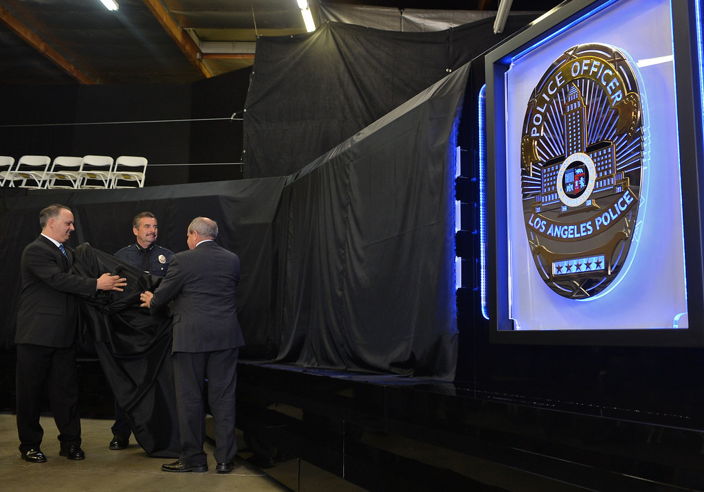 . The Los Angeles Police Protective League and the Eagle & Badge Foundation unveiled new End of Watch Memorial Wall featuring the names of the 206 officers who have died in the line of duty. The 60 ft. wide and 9 ft tall wall was made at Commemorative Badge Company in Gardena where it was unveiled. LAPD Chief Charlie Beack admires badge during unveiling.       Photo by Robert Casillas / Daily Breeze