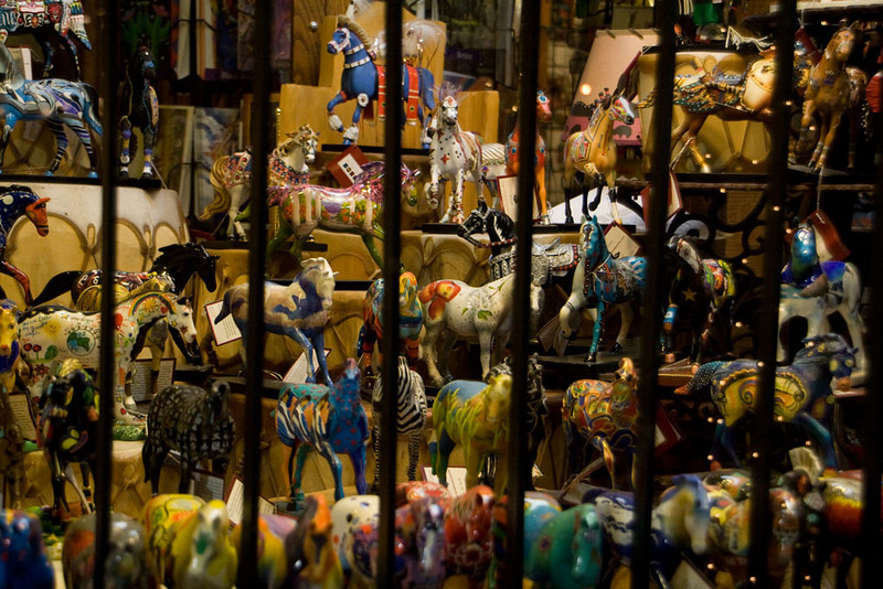 """A few years ago, there was a public art project named """"Trail of Painted Ponies"""". Artists were given life sized horse figures to paint or adorn as they wished. Now there are miniature reproductions of the figures available for sale, with all sorts of art styles represented. A number of businesses sell them. This shop has quite a large collection."""