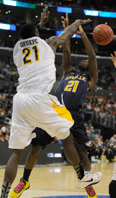 . Wichita #21 Ehimen Orukpe blocks a shot by La Salle #21 Tyrone Garland in the first half. La Salle played Wichita State at Staples Center for the West Regional of the NCAA Division I Men\'s Basketball Championships. Los Angeles,CA 3/28/2013(John McCoy/Staff Photographer