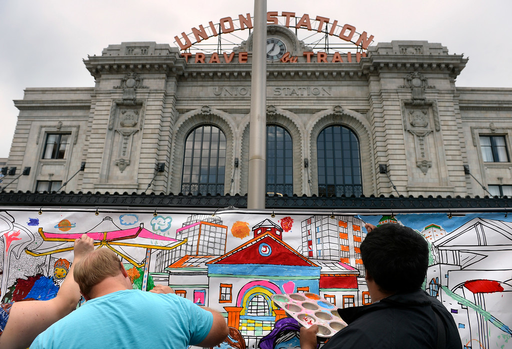 . Visitors are encouraged to paint on a paper mural outside the station. Denver Union Station hosts a public event for their grand opening celebration featuring food trucks and live music on Wynkoop Street and free tours of the building. (Photo by Kathryn Scott Osler/The Denver Post)