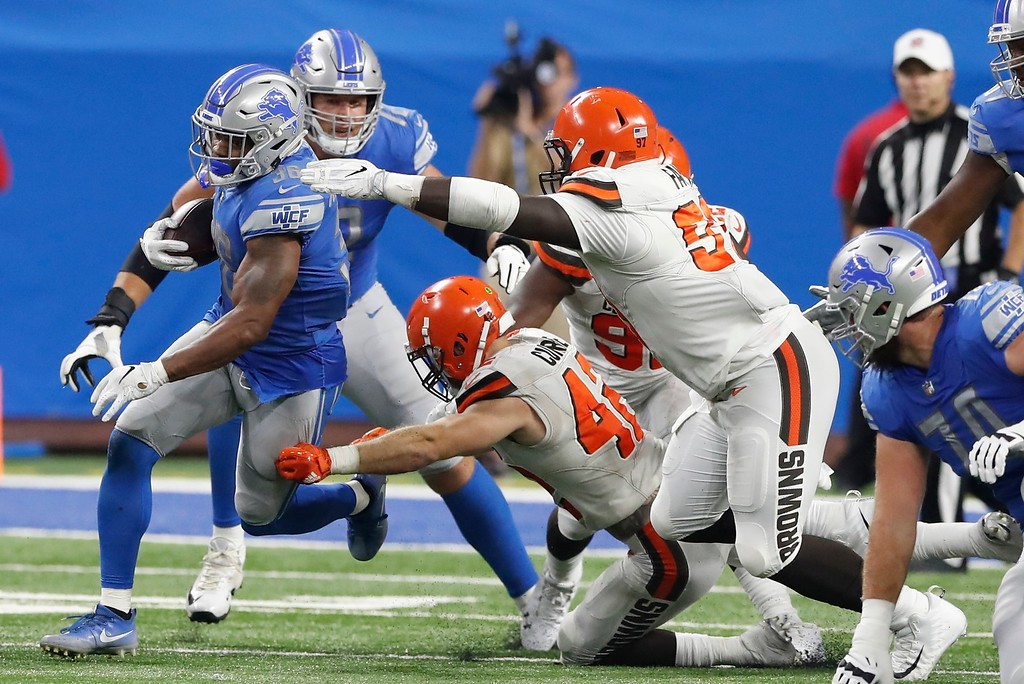 . Cleveland Browns linebacker Justin Currie (42) and defensive tackle Jeremy Faulk (97) reach in to stop Detroit Lions running back Dwayne Washington during the second half of an NFL football preseason game, Thursday, Aug. 30, 2018, in Detroit. (AP Photo/Carlos Osorio)