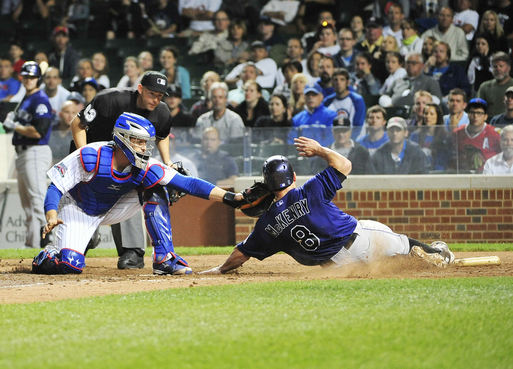 . CHICAGO, IL - JULY 30: Michael McKenry #8 of the Colorado Rockies is tagged out by John Baker #12 of the Chicago Cubs during the tenth inning on July 30, 2014 at Wrigley Field in Chicago, Illinois. (Photo by David Banks/Getty Images)