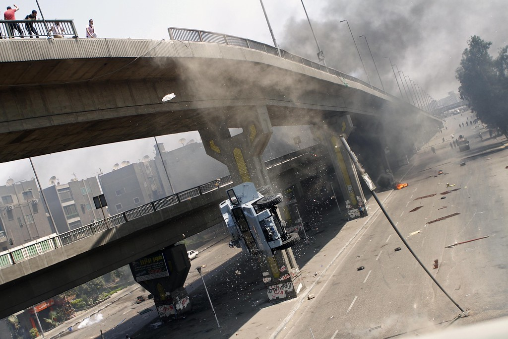 . A police vehicle is pushed off of the 6th of October bridge by protesters close to the largest sit-in by supporters of ousted Islamist President Mohammed Morsi in the eastern Nasr City district of Cairo, Egypt, Wednesday, Aug. 14, 2013.   (AP Photo/Sabry Khaled, El Shorouk Newspaper)