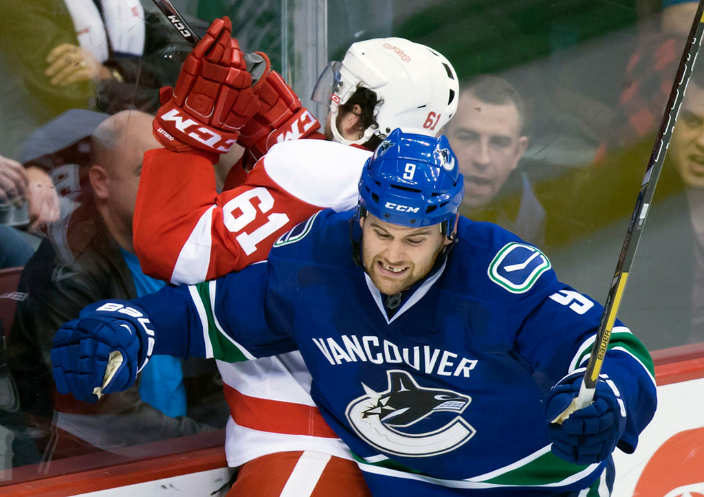 . Vancouver Canucks\' Zack Kassian (9) checks Detroit Red Wings\' Xavier Ouellet (61) during the third period of an NHL hockey game in Vancouver, British Columbia on Saturday, Jan. 3, 2015. (AP Photo/The Canadian Press, Darryl Dyck)