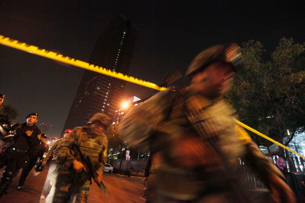 . Soldiers are seen on a street outside the headquarters of state oil giant Pemex in Mexico City January 31, 2013. A powerful explosion rocked the Mexico City headquarters of Pemex on Thursday, killing at least 14 people and injuring 100 others.The blast hit the lower floors of the downtown tower block, throwing debris into the streets and sending workers running outside. It was not yet clear what caused the explosion, and the death toll could still rise. REUTERS/Edgard Garrido